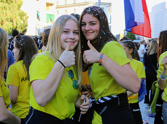 happy french girls covered with confetti at girls at women's football tournament