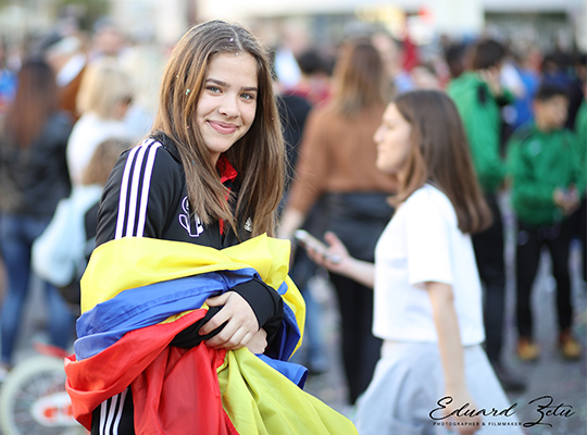 happy soccer girl covered with romanian flag